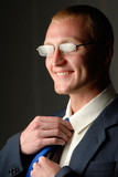 portrait of  businessman correcting  tie on  dark background poster
