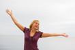 eine junge unbeschwerte glückliche frau in einer jubelnden pose
