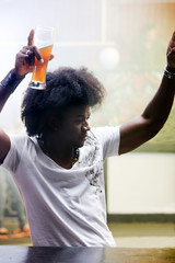 man dancing in a bar or a nightclub with a beer on his hand