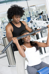 Afro american couple doing fitness exercises in the gym.