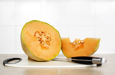 cantaloupe and knive on cutting board