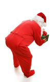 Santa Claus in footy pajamas, bending over to pick up gift poster
