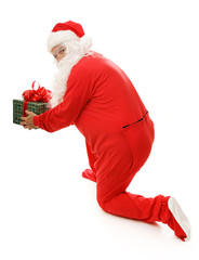 Santa Clause in his pajamas caught setting down a gift.