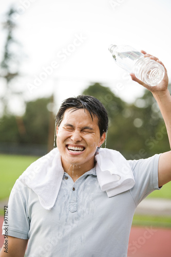 An asian male pouring water on top of his head after exercise