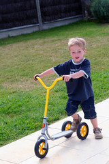 petit garçon roulant à la trottinette
