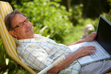 Happy senior man is his elderly 70s sitting outdoor in garden