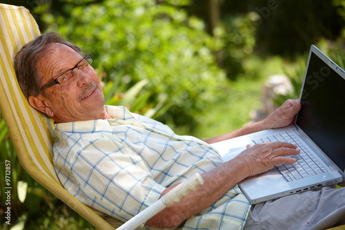 Happy senior man is his elderly 70s sitting outdoor in garden