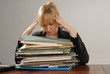 stressed businesswoman executive with stack of paper