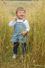 little girl runs across the field of a rye