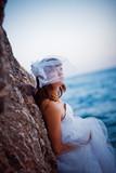 Portrait of bride in wedding dress staying near rock poster