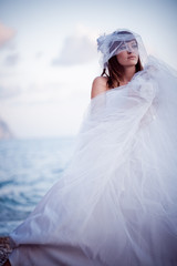 Posing fashion bride in wedding dress outdoors