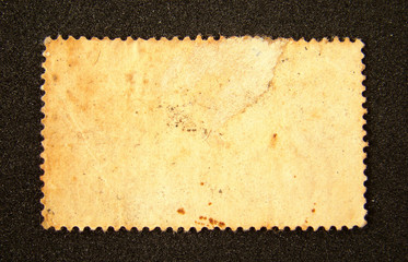 Old blank postage stamp on black background