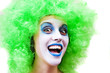 spooky female clown in heavy stage make-up