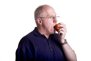 An older guy in a blue shirt on a white background eating