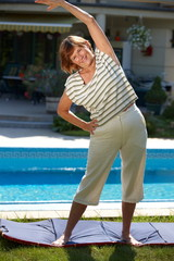 Happy active senior woman doing workout exercise at home,