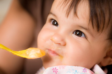 Mother feeding baby girl with spoon.