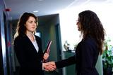 Businesswomen shaking hands at office corridor. poster