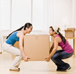 Women moving into new home and carrying large cardboard box