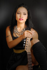 female rocker with guitar and dramatic lighting