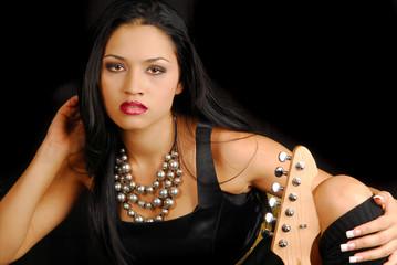 Attractive hispanic female rocker with her guitar