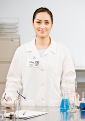 Research scientist in lab coat testing specimens in laboratory