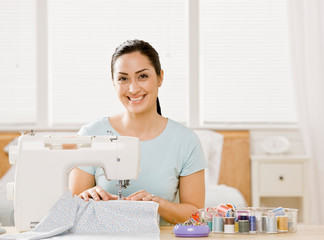 Self-sufficient woman using sewing machine to make clothing