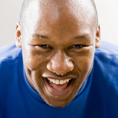 Fatigued man smiling and dripping sweat