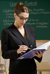 Teacher wearing eyeglasses reading text book in classroom