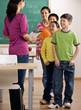 Students listen to teacher with clipboard in school classroom