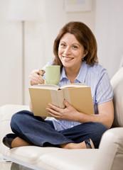 Woman sitting on sofa in livingroom enjoying reading book