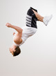 Skilled athlete in sportswear doing somersault in mid-air
