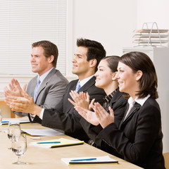 Co-workers applauding in meeting in conference room