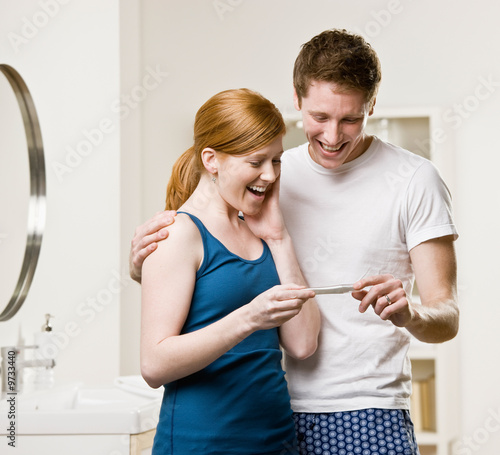 Happy couple in bathroom viewing positive pregnancy test
