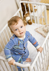 Determined toddler boy trying to climb out of crib in bedroom