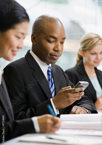 Businessman text messaging on cell phone in conference room