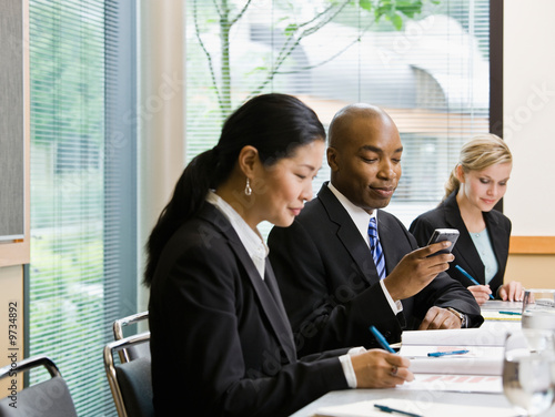 Businessman with co-workers text messaging on cell phone