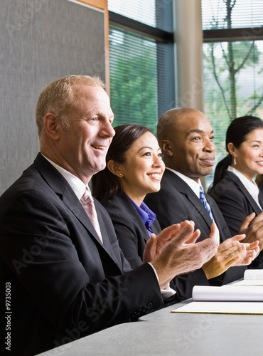 Multi-ethnic co-workers sitting in a row, applauding at table