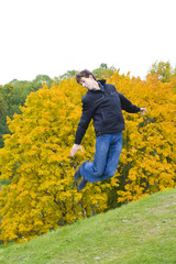 The guy cheerfully jumps against a tree with yellow leaves