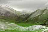 Green grassy mountains with sprinkling of snow covering them poster