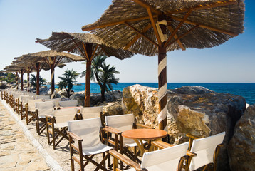 Welcoming beach cafe with straw parasols. Samos Island, Greece