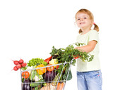 Happy healthy little girl with vegetables in shopping cart