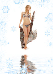 walking bikini blonde girl with sarong on white sand