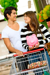Beautiful couple smiling - savings - shopping in supermarket