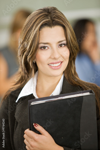 Beautiful business woman with a folder in an office