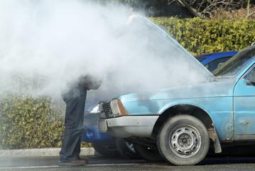 Man looking at a smoking engine in his car