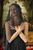 very cute widow in black dress and veil on face inside a church