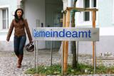 Junge Frau vor Gemeindeamt mit Sturzhelm