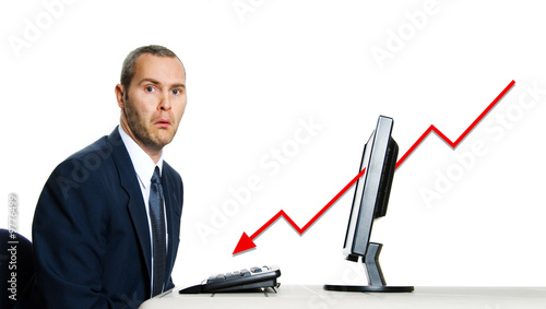 unhappy man in blue suit at office computer financial crisis