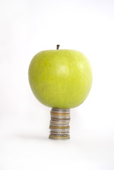 Green apple on the pile of coins