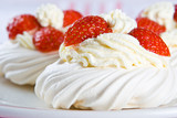 Fresh meringue with thick cream and stawberries on a plate poster